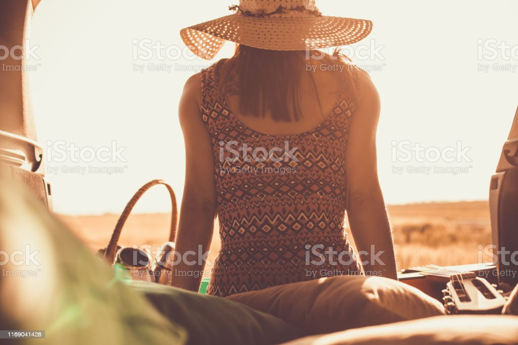 Rear view of young woman sitting in the back of the car set up for...