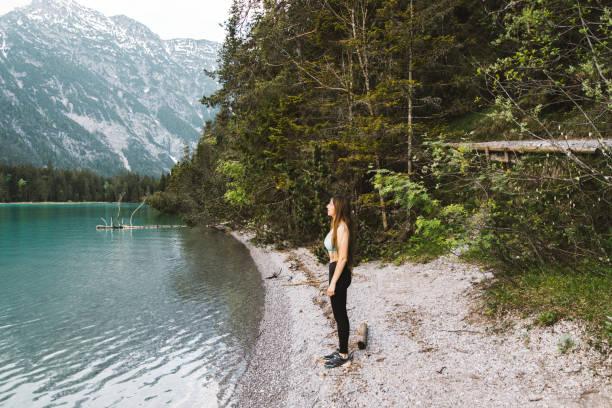 frau genießt sommersonnenuntergang am plansee in den österreichischen alpen - spitzen crop tops stock-fotos und bilder
