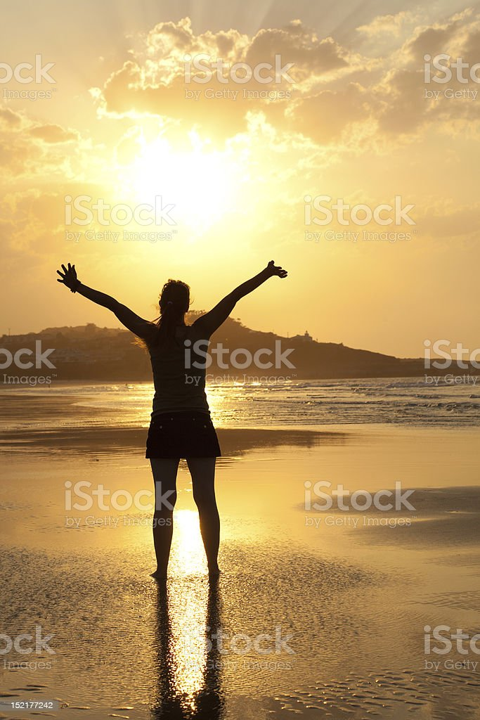woman enjoying sun in a deserted beach at sunset royalty-free stock photo