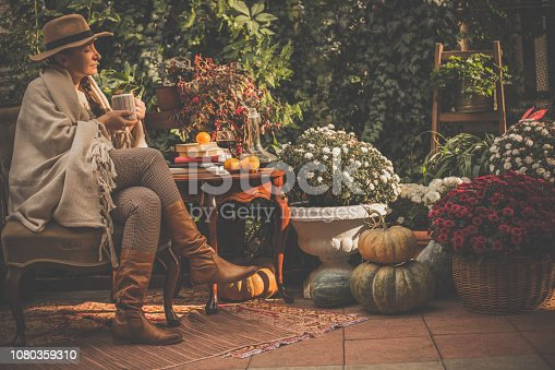 Side view of a woman sitting and relaxing with a cup of hot beverage in back yard. She is enjoying autumn day surrounded by flowers and plants.
