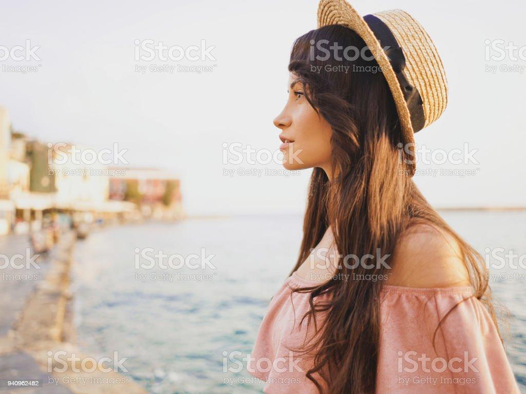 Woman enjoying sunrise on seafront in old european town stock photo