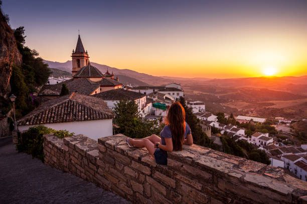 Woman enjoying sunset from Zahara de la Sierra in Spain stock photo