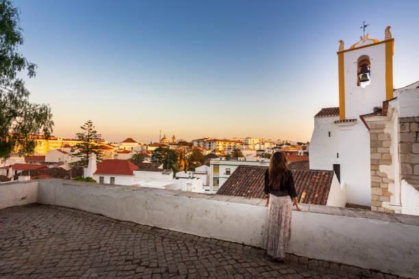Woman enjoying sunset near Santiago Church (Igreja de Santiago) in Tavira, Portugal stock photo