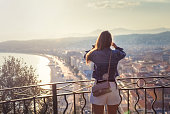 Woman tourist njoying sunset looking at view of Nice, France. Summer holidays vacation.