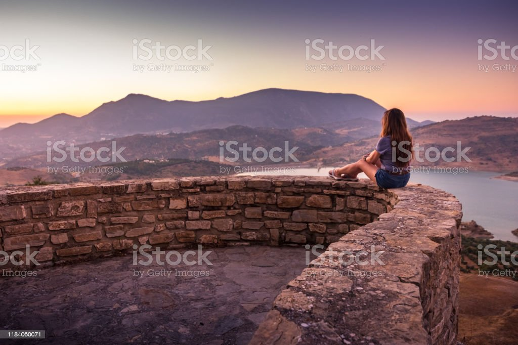 Woman enjoying sunset view of Zahara-El Gastor Reservoir from Zahara de la Sierra in Spain - Royalty-free Adult Stock Photo