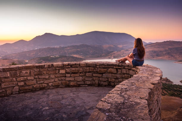 Woman enjoying sunset view of Zahara-El Gastor Reservoir from Zahara de la Sierra in Spain stock photo