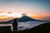 One woman, standing high on beautiful mountain Batur in sunset alone.