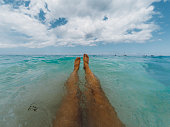 Woman taking photo of her legs lying in the turquoise ocean enjoying her beach holiday on Zanzibar