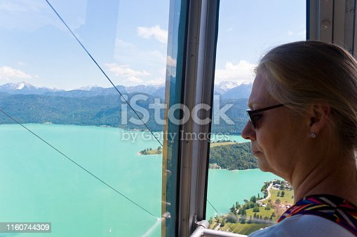Blond woman enjoying the breathtaking view from a cabin of a cable car