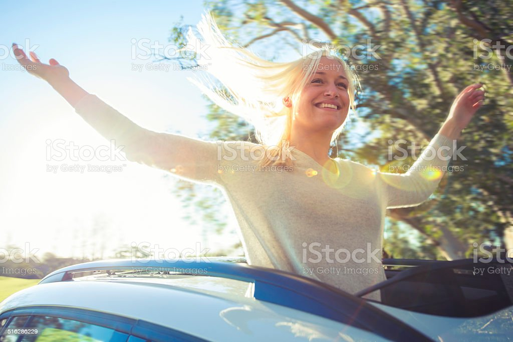 Woman enjoying the freedom of a sun roof stock photo