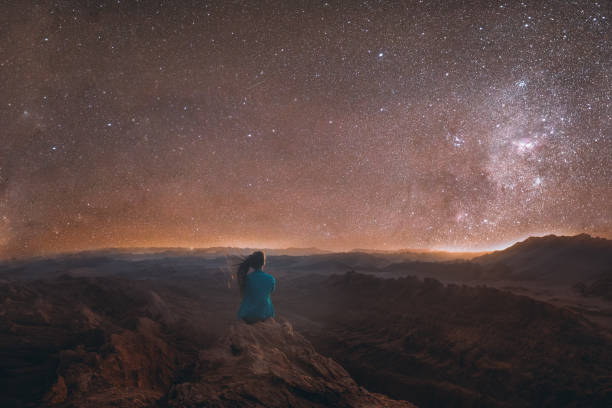 Woman enjoying the scenic view of the million stars above the big canyon at Atacama desert, Chile stock photo