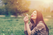 Young woman blowing out dandelion