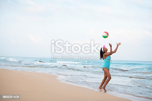 Attractive woman catching an inflatable ball, playing on the sea beach on water's edge during her summer vacation. The woman wearing a blue retro style swimsuit with polka dots, and sun visor.