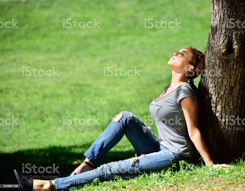 Woman enjoying the sun in the park stock photo