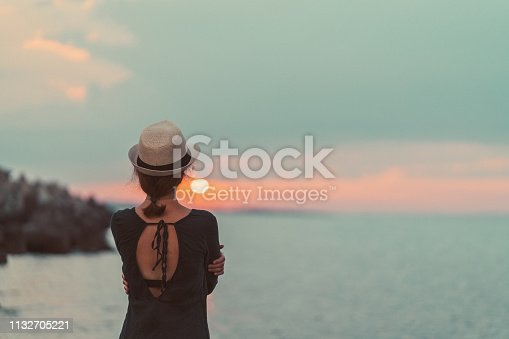 Rear view of woman with sun hat staring the sunset over the water