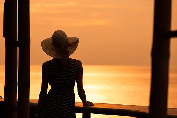 Woman enjoying the sunset Woman enjoying beautiful sunset from the balcony.  sun shining through dresses stock pictures, royalty-free photos & images