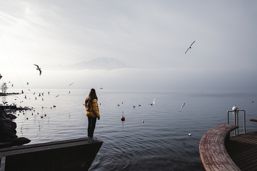 Woman enjoying the view of Swiss Alps, lake Geneva and flying birds in Montreux