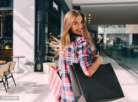 Happy girl with shopping bags looking over shoulder