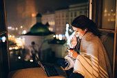Woman staying home at New Year's eve and talking with her mother on video call