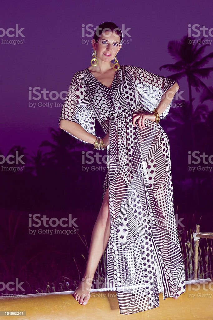 Woman enjoying tropical vacation Portrait of beautiful woman wearing summer dress posing with coconut palm tress in the background. Looking at camera and smiling. 30-34 Years Stock Photo