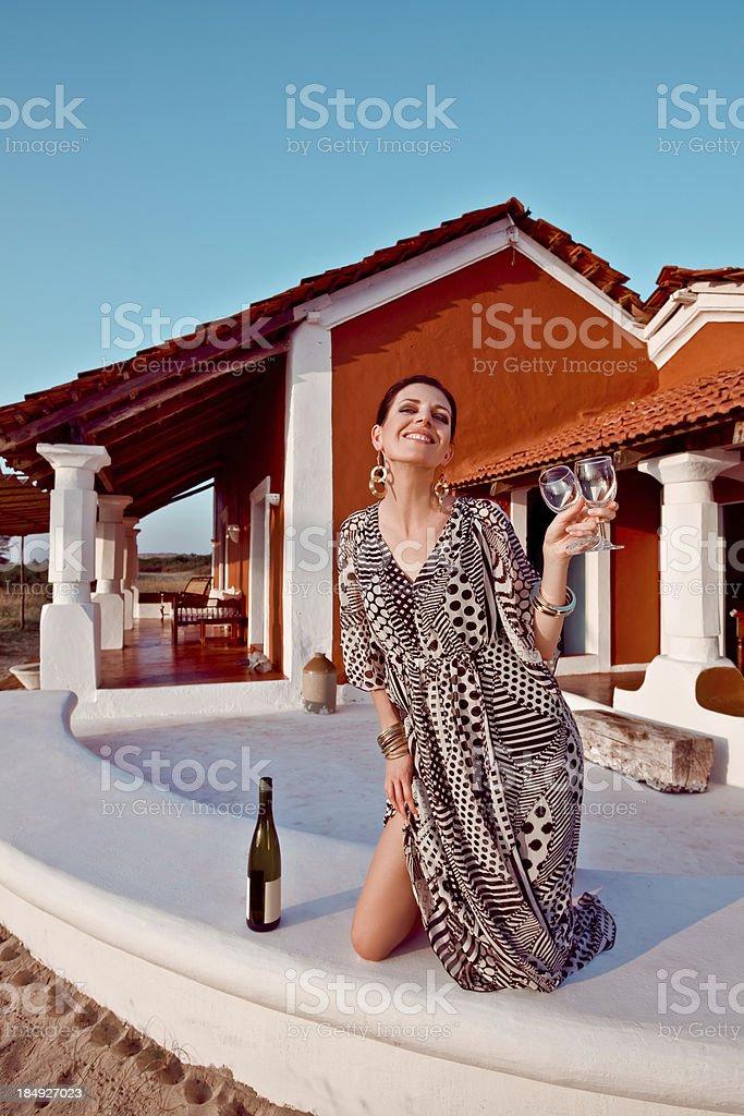 Woman enjoying tropical vacation with wine Happy beautiful woman wearing summer dress, holding wine glasses and enjoying her tropical vacation. 30-34 Years Stock Photo