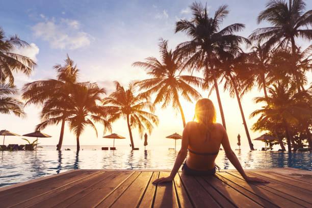kobieta korzystających wakacje luksusowe hotelowy basen przy plaży - kurort turystyczny zdjęcia i obrazy z banku zdjęć