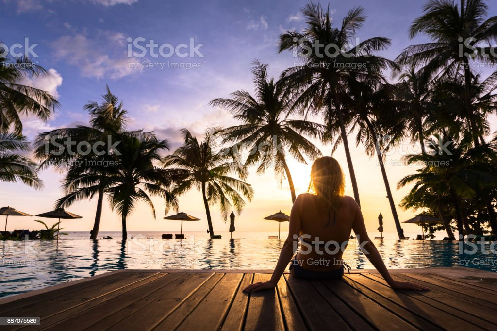 Woman enjoying vacation holidays luxurious beachfront hotel resort swimming pool stock photo
