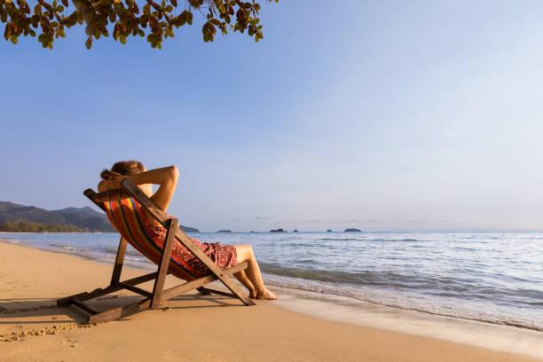 Frau genießt Urlaub am Strand und entspannt sich im Liegestuhl am Meer, warmer, sonniger Sommertag zum Ausruhen und Sonnenbaden – Foto