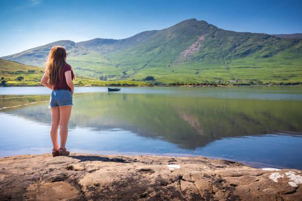Woman enjoying view at Killary Harbour fjord in Leenane - Connemara, Ireland stock photo