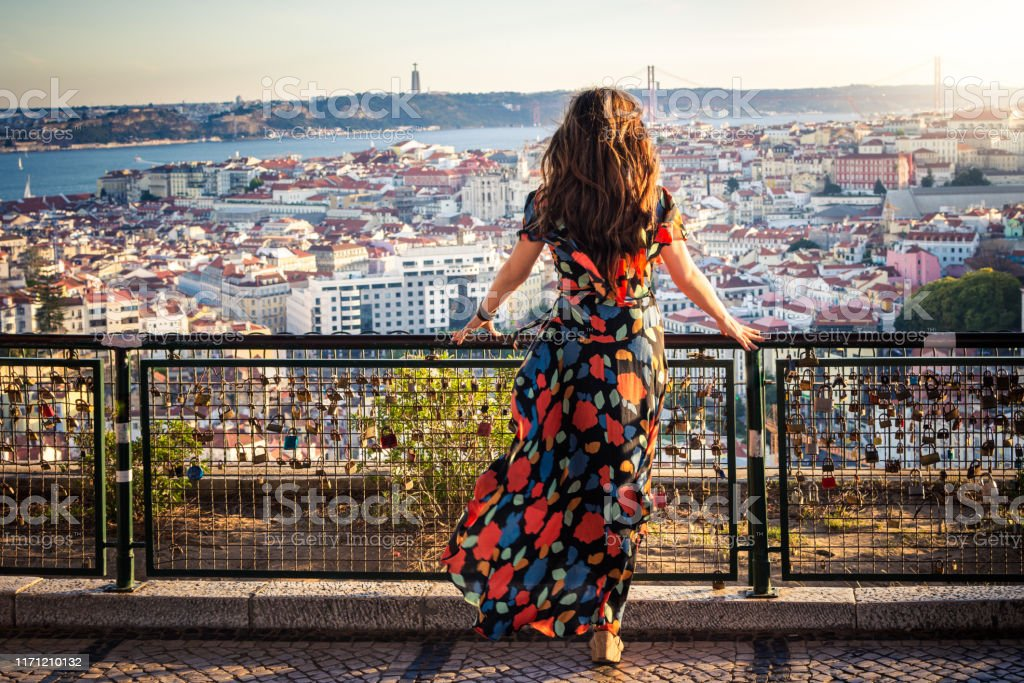 Woman enjoying view from Miradouro da Senhora do Monte in Lisbon, Portugal Perched upon a hillside in the Graca neighborhood, Miradouro da Senhora do Monte provides tourists and locals spectacular views of the Tagus River, Castle of Saint George and the 25 de Abril Bridge. Adult Stock Photo