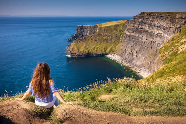 Woman enjoying view of Cliffs of Moher in Ireland during a sunny Summer's day stock photo