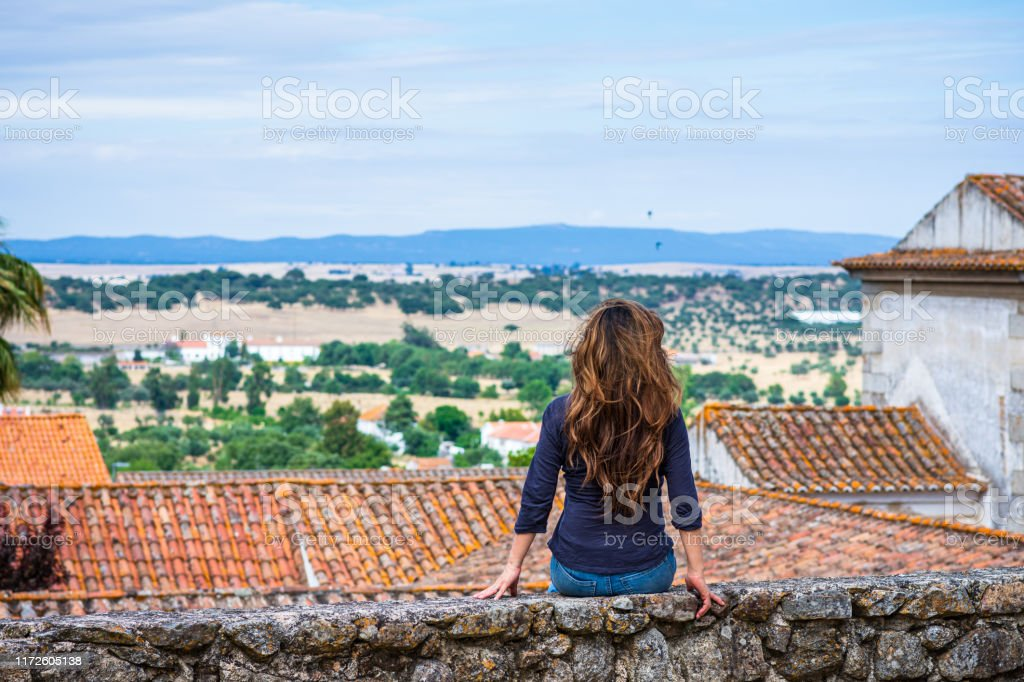 Woman enjoying view of countryside near University of Évora, Portugal The University of Évora (Universidade de Évora) is a public university in Évora, Portugal. It is the second oldest university in the country, established in 1559. Shot from the patio across the street - Pateo de Sao Miguel. 40-49 Years Stock Photo