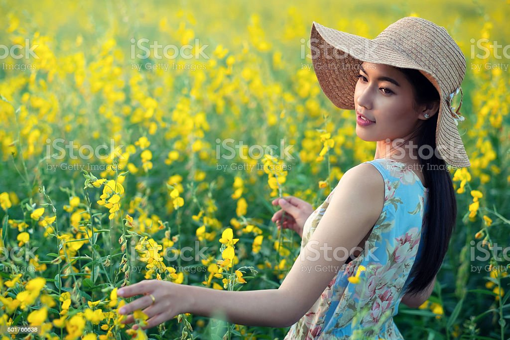 woman enjoying with flowers on field stock photo