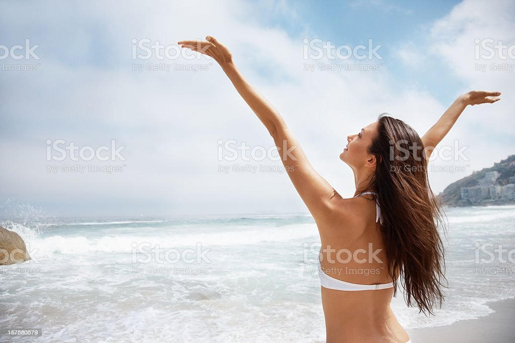 Woman enjoying with hands raised on the beach royalty-free stock photo