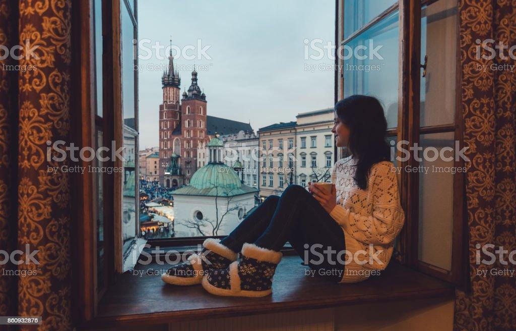 Woman enjoyng Krakow city from the window stock photo