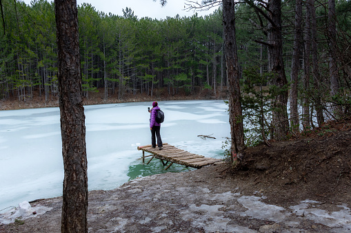 629376126 istock photo A woman enjoys a calm frozen lake located deep in the forest 1222728339