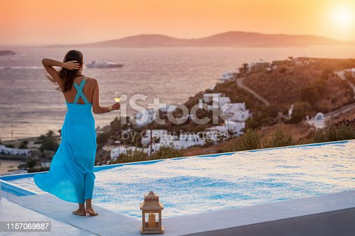 Beautiful woman in a summer dress enjoys a glass of wine by the pool with view to the Mediterranean sea during sunset time, Mykonos, Greece