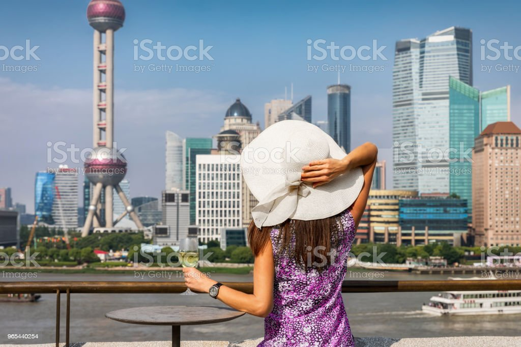 Woman enjoys a glass of wine in front of the skyline of Shanghai royalty-free stock photo