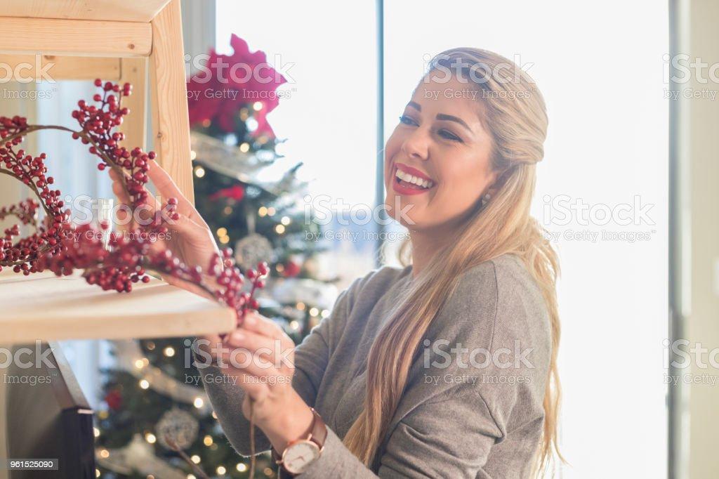 Woman enjoys decorating home for Christmas stock photo