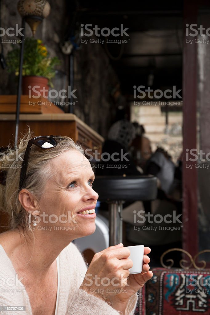 Woman enjoys espresso at streetside cafe stock photo
