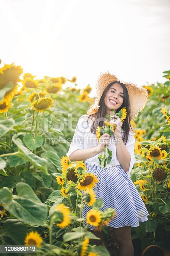 Woman enjoys in sunflower field