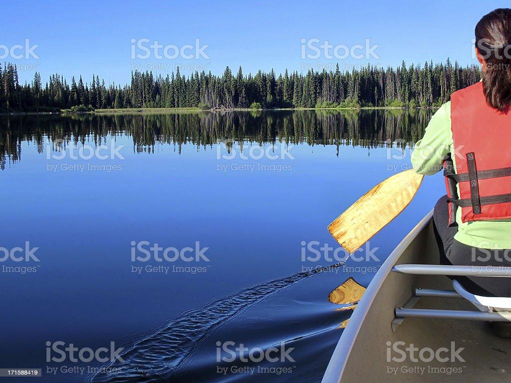 Woman enjoys nature while canoeing royalty-free stock photo