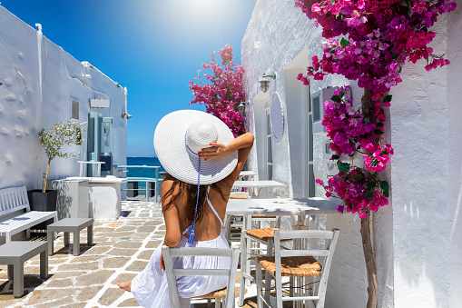 Woman enjoys the classic setting of white houses and colorful flowers on the cyclades islands of Greece
