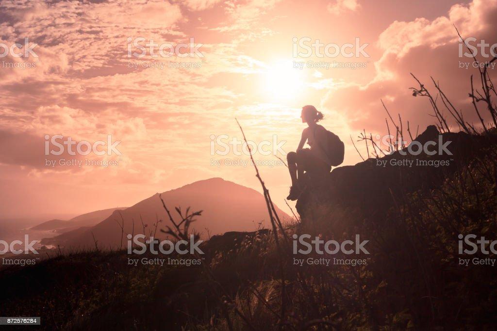 Woman enjoys the view at mountain peak stock photo