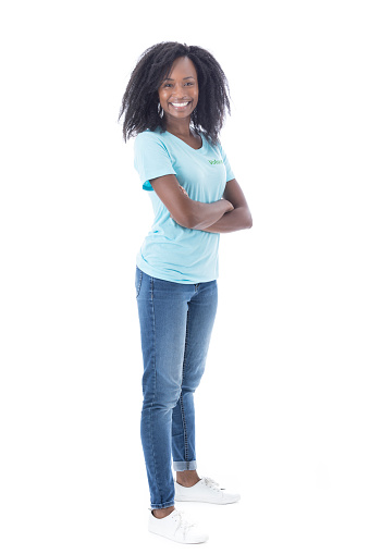 Mid adult African American female volunteer stands confidently with her arms crossed while looking at the camera.