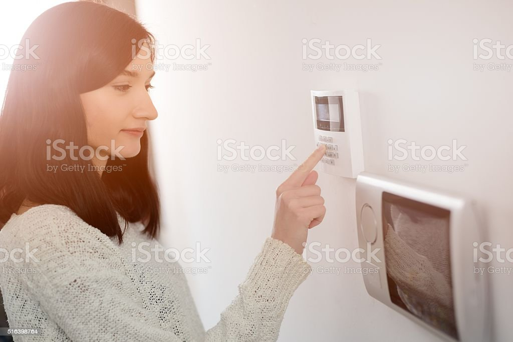 woman entering code on keypad of home security alarm​​​ foto