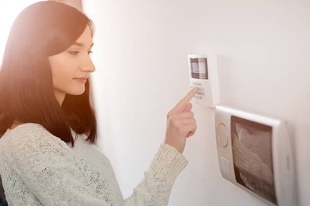 woman entering code on keypad of home security alarm - alarm stock pictures, royalty-free photos & images