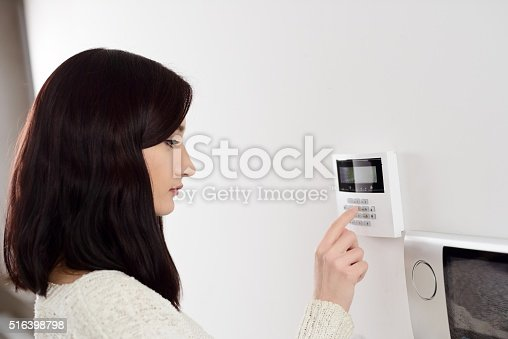 istock woman entering code on keypad of home security alarm 516398798