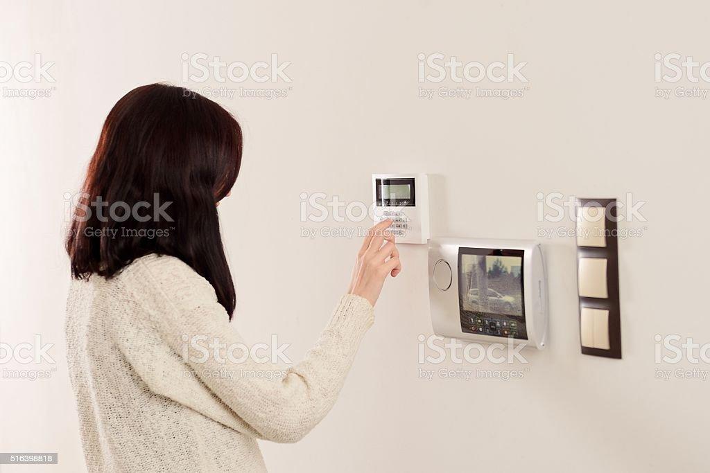 Femme entrant le code sur clavier d'alarme de sécurité à la maison - Photo