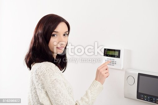 istock woman entering code on keypad of home security alarm 516398922